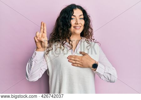 Young brunette woman with curly hair wearing casual clothes smiling swearing with hand on chest and fingers up, making a loyalty promise oath