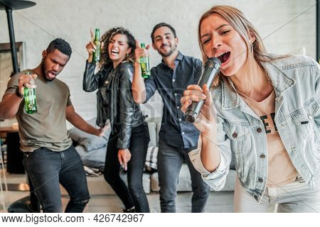 Group Of Friends Playing Karaoke At Home.