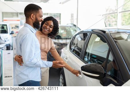 Car Choosing. Happy Black Spouses Standing Next To Modern Vehicle In Showroom