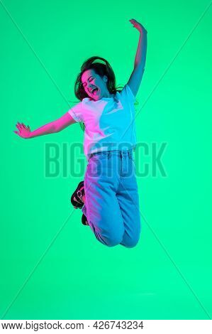 Full-length Portrait Of Joyful Young Beautiful Girl, Female Model Jumping High Isolated On Green Bac