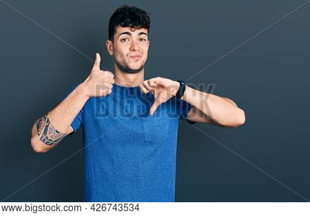 Young hispanic man wearing casual t shirt doing thumbs up and down, disagreement and agreement expression. crazy conflict