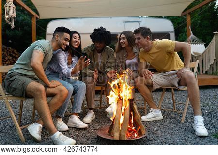 Group Of Cheerful Diverse Friends Spending Time Near Bonfire, Having Camping Vacation With Rv, Havin