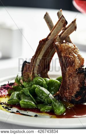 Grilled Rack Of Lamb, Close-up. Lamb Bone Medallions From The Chef, Tender Lamb Meat On A Light Plat