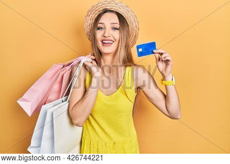 Young blonde girl holding shopping bags and credit card smiling and laughing hard out loud because funny crazy joke.