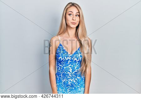 Young beautiful caucasian woman wearing summer dress smiling looking to the side and staring away thinking.