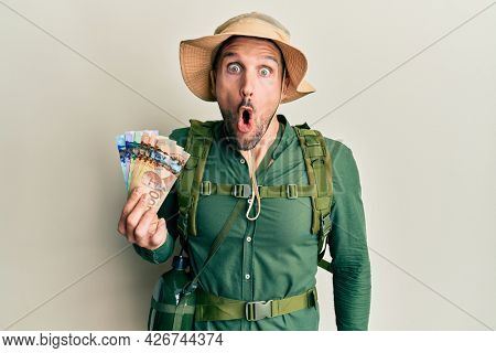 Handsome man with beard wearing explorer hat holding canadian dollars scared and amazed with open mouth for surprise, disbelief face