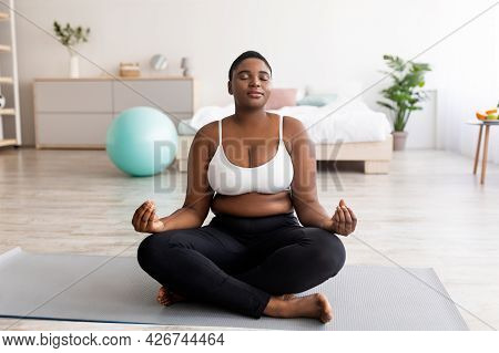 Plus Size Black Woman Sitting In Lotus Pose, Meditating With Closed Eyes, Practicing Yoga At Home