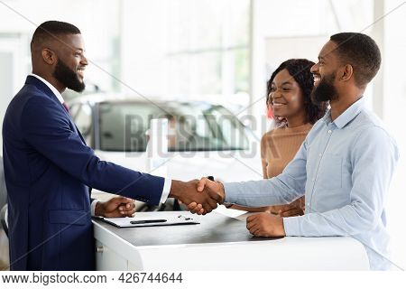 Buying New Car. African Couple Shaking Hands With Salesman In Dealership Center