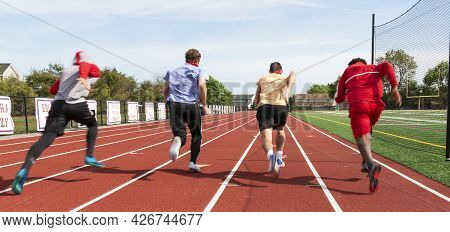 Rear View Of High School Boys Sprinting Down The Track In Lanes Racing Each Other During Practice.al