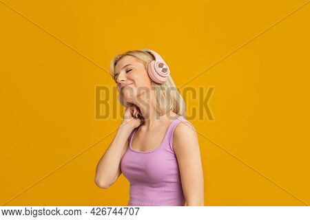Carefree Mood. Happy Lady Enjoying Music In Headphones, Listening Favorite Songs With Closed Eyes, Y
