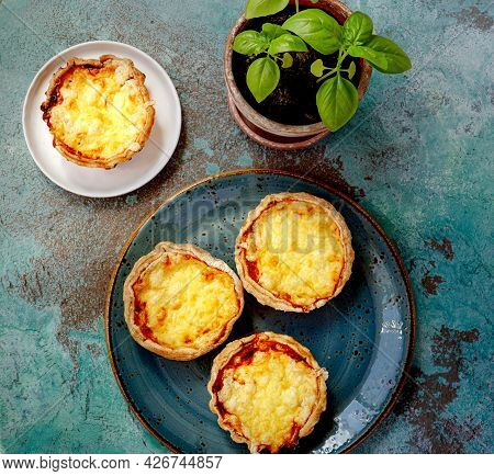 Mini Quiches On A Blue Plate. Flaky Dough Pies. Fresh Basil And Mini Quiches On A Blue Background.