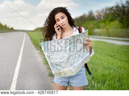 Stressed Female Tourist With Map Standing On Roadside, Speaking On Smartphone, Cannot Catch Car Or F