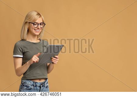 App For Students. Excited Young Lady With Newest Digital Tablet, Surfing Internet On Beige Backgroun