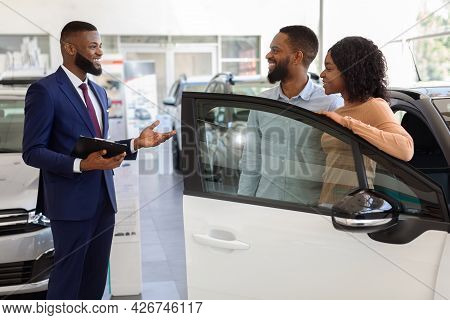 Salesman At Car Dealership Center Helping Spouses To Choose New Family Vehicle