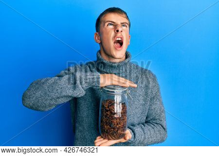 Young caucasian man holding jar of raisins angry and mad screaming frustrated and furious, shouting with anger looking up.