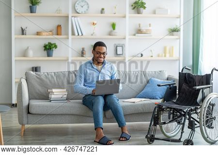 Handicapped Black Freelancer In Wheelchair Doing Work Project, Speaking With Boss, Having Online Con