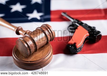 Concept Showing Of Us Or American Gun Laws With Judge Gavel And Vintage Pistol On American Flag