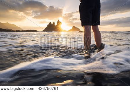 Low Section Of Man During Relaxation In Ocean. Scenic View Of Benijo Beach Against Sky At Beautiful