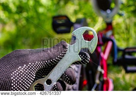 Wrench In Hand. Bicycle Repair. Gloved Hands Hold The Bicycle Key. Bicycle Service.