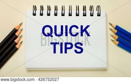 On A Light Background, A White Notebook With The Text Quick Tips And Black And Blue Pencils On The S