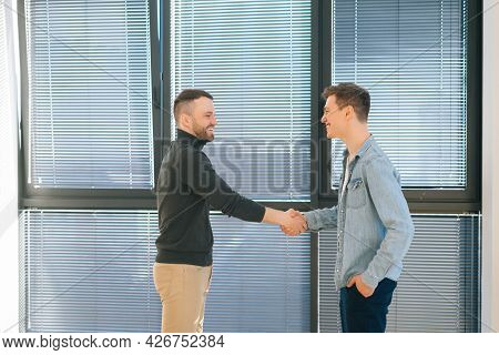 Side View Of Manager Wearing Casual Clothes Shake Hand Of Man Client Or Customer Making Business Dea