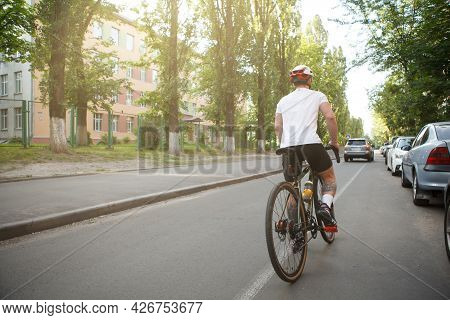 Rear View Full Length Shot Of A Male Cyclist In Bike Helmet Riding Bicycle In The City