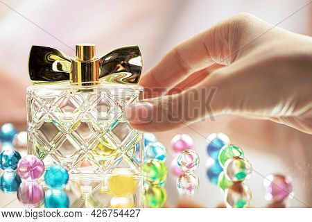 A Womans Hand Puts A Perfume Bottle On A Glass Surface With Glass Colored Balls. Perfumes, Cosmetics