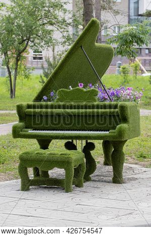 A Flowerbed In The Form Of A Grand Piano, Covered With Synthetic Grass With Flowering Petunias Under