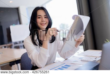 Beautiful Asian Business Lady Holding Paperwork, Pencil And Smiling Looking At Camera While Working