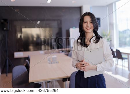 Portrait Of Asian Young Beautiful Business Woman In The Office. Crossed Arms And Holding Files, Docu