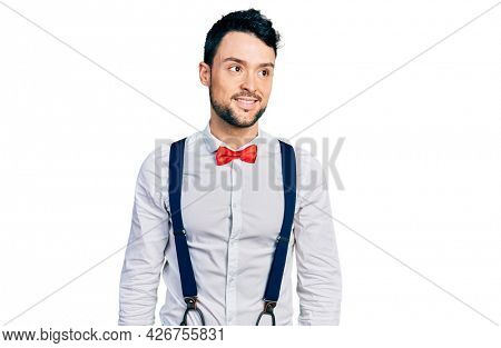 Hispanic man with beard wearing hipster look with bow tie and suspenders looking away to side with smile on face, natural expression. laughing confident.