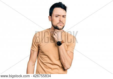 Hispanic man with beard wearing casual t shirt touching painful neck, sore throat for flu, clod and infection