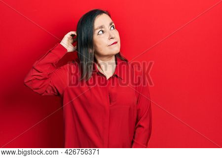Middle age hispanic woman wearing casual clothes confuse and wondering about question. uncertain with doubt, thinking with hand on head. pensive concept.