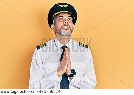 Handsome middle age man with grey hair wearing airplane pilot uniform begging and praying with hands together with hope expression on face very emotional and worried. begging.