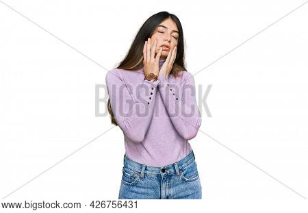 Young beautiful teen girl wearing turtleneck sweater tired hands covering face, depression and sadness, upset and irritated for problem
