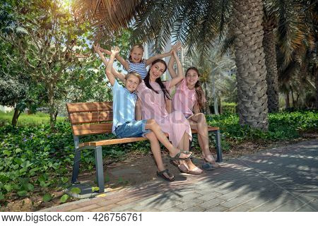 Happy Mother and Her Three Precious Kids Sitting on the Bench in the Park. Big Family Having a Good Time in City Park on Summer Day. Love Concept.