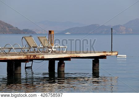 Empty Pier With Deck Chairs On Sea And Misty Mountains Background. Summer Vacation And Tanning On A