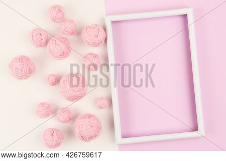 A White Empty Frame And A Lot Of Pink Balls Of Yarn For Knitting Or Crocheting On A White And Pink B