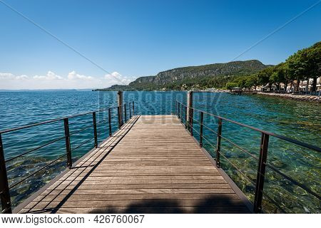 Wooden Pier On Lake Garda (lago Di Garda) In Front Of The Small Town Of Garda, Bay With The Headland