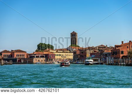 Murano Island, Famous For The Production Of Artistic Glass With A Canal With Two Ferry Boats And The