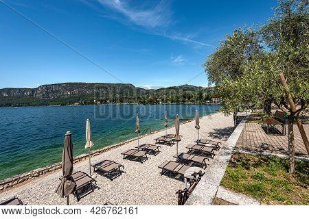Beach Umbrellas And Empty Deck Chairs On A Beautiful Beach On Lake Garda (lago Di Garda). Garda Town