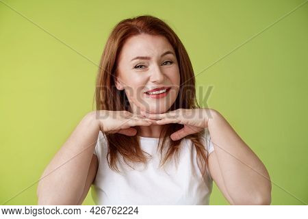 Looking Good. Happy Cheerful Redhead Middle-aged 50s Woman Smiling Delighted Hold Hands Under Chin A
