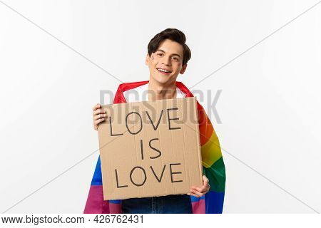 Smiling Gay Man Activist Holding Sign Love Is Love For Lgbt Pride Parade, Wearing Rainbow Flag, Stan