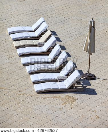 Empty Lounge Chairs In A Row With Beach Umbrella On A Paver Decking