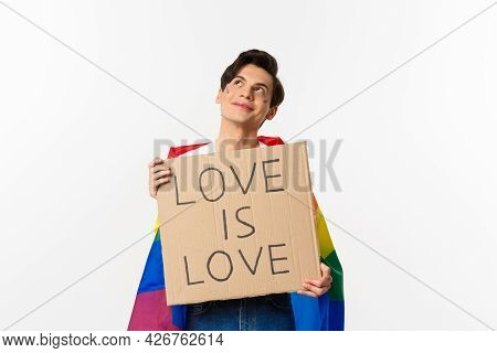 Dreamy Young Queer Person Smiling And Looking At Upper Left Corner, Holding Love Is Love Sign For Pr