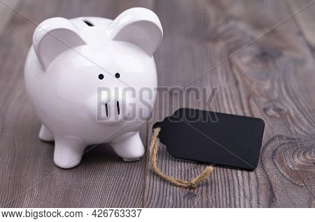 The Photo Shows A Piggy Bank With A Blank Slate, Which Provides Space For Text