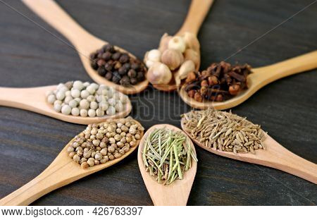Closeup Of Assorted Aromatic Spices In Wooden Spoons With Selective Focus