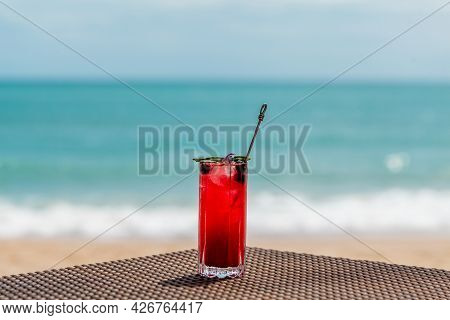 Cold Fresh Red Berries Mocktail With Ice Cubes On Beach Table, Defocused Turquoise Sea On Background