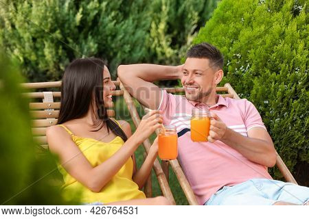 Happy Couple With Mason Jars Of Refreshing Drink Resting In Deck Chairs Outdoors