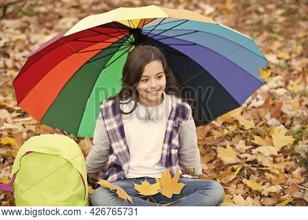 Perfect Autumn Day Of Cheerful Child Under Colorful Umbrella With School Bag Sitting In Fall Season